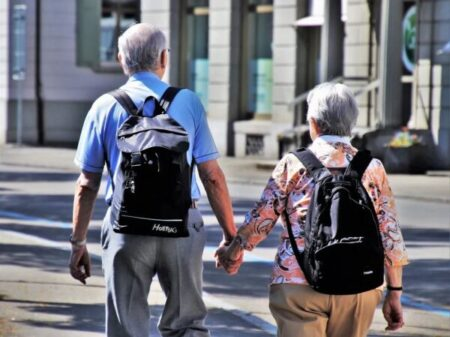 Two people walking with backpacks, probably traveling
